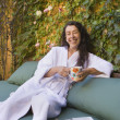 Middle-aged woman in bathrobe drinking coffee outdoors - Stock Photo