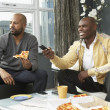 African men watching television and eating pizza in living room — Stock Photo