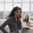 Trinidadian businesswoman talking on cell phone in office — Stock Photo