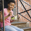 African woman sitting on steps eating salad — Stock Photo