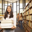 Teenaged Asian girl carrying books in library — Stock Photo