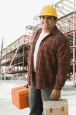 Hispanic construction worker carrying toolbox and lunch box — Stock Photo