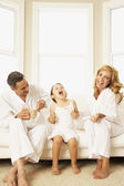 Hispanic family laughing on sofa — Stock Photo