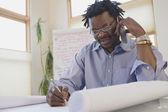 Arquiteto africano trabalhando em projetos e falando no celular — Foto Stock