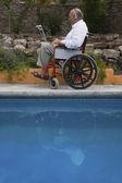 Senior man using laptop in wheelchair — Stock Photo