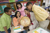 African teacher and students looking at globe — Stock Photo