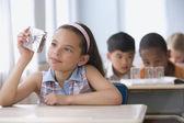 Hispanic girl looking at spider specimen in plastic — Stock Photo