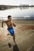 Bare chested Asian man jogging along urban waterfront — Stock Photo