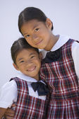 Asian sisters in school uniforms hugging and smiling — Stock Photo