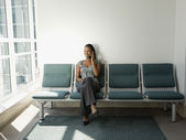 African woman talking on cell phone in waiting room — Stock Photo
