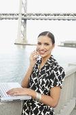 Spansktalande kvinna talar i mobiltelefon och använda laptop utomhus — Stockfoto