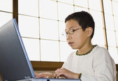Asian boy typing on laptop — Stock Photo