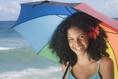 African woman at beach with umbrella — Stock Photo