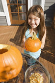 Mixed race young girl holding Halloween pumpkin — Stok fotoğraf