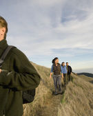 Multi-ethnic friends hiking on hillside — Stock Photo
