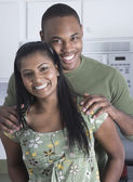 Multi-ethnic couple standing in kitchen — Stock Photo