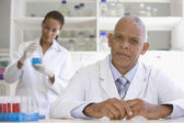 African scientist in laboratory with co-worker in background — Stock Photo