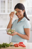 Indian woman holding salad and cucumber — Stock Photo