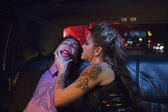 Dominatrix and man wearing ball gag in limousine — Stock Photo