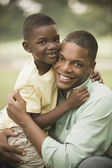 African father hugging son outdoors — Stock Photo
