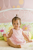 Mixed race baby girl sitting on bed — Stock Photo