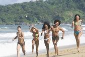Multi-ethnic friends running on beach — Stock Photo