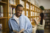 African teenage boy reading in school library — Stock Photo