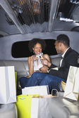 African couple toasting with champagne in limousine — Stockfoto