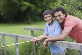 Mixed race father and son fishing on bridge — Stockfoto