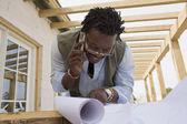 Homem africano no celular olhando plantas — Fotografia Stock