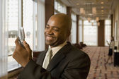 African businessman looking at cell phone in corridor — Stock Photo