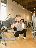 Trainer helping man exercise in health club — Stock Photo