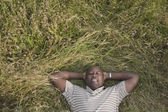 African man relaxing in grass — Stock Photo