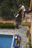 Senior woman dropping laptop from balcony — Stock Photo