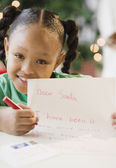 African American girl writing letter to Santa Claus — Stock Photo