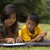 Asian mother reading book to son — Stock Photo