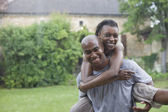 African couple playing in the rain — Stock Photo