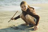 Hispanic girl drawing in sand — Stock Photo