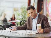 Businessman reading newspaper at cafe — Stock Photo