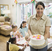 Hispanic mother holding cake at daughter's birthday party — Stock Photo