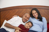 Boy lounging in bed with parents — Stock Photo