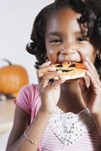 African girl eating Halloween cookie — Photo