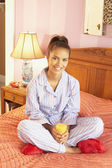 Hispanic woman in pajamas holding orange juice — Stock Photo