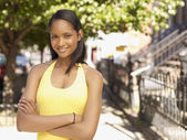 African woman outdoors with arms crossed — Stock Photo