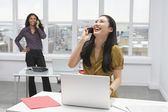 Korean businesswoman talking on cell phone in office — Stock Photo