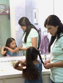 Hispanic mother braiding daughter's hair — Stock Photo