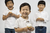 Korean children eating cupcakes — Stock Photo
