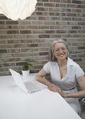Portrait of senior woman next to laptop — Stock Photo