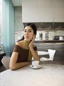Spansktalande kvinna sitter på café med kaffe — Stockfoto
