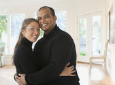 Couple hugging in living room — Stock Photo